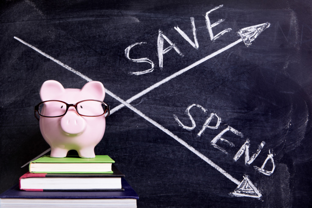Pink piggy bank with glasses standing on books next to a blackboard with simple spend and save message. Sharp focus on the piggy bank with blackboard slightly blurred.